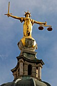 Scales of Justice statue on top of The Old Bailey central criminal court, London, UK Designed by E W Mountford