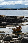 Traditional wooden rowing boat beached on a rocky Island in Norway