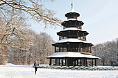Jogger near snow-covered Chinese Tower, English Garden, Munich, Bavaria, Germany