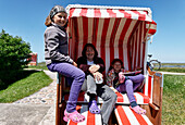 Mother and two daughters sat on a canopied beach chair on the Lorenzwarft, Hallig Hooge, North Sea, Schleswig-Holstein, Germany