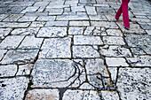 Women wearing red trousers walking down a large stone street, Split, Croatia, Europe