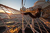 Woman relaxing in bowsprit net of sailing cruiseship Star Flyer (Star Clippers Cruises) at sunset, Pacific Ocean, near Costa Rica, Central America, America