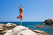 Woman exercising Yoga on the rocks of Palombaggia beach, south-east coast, Balagne region, Corsica, France, Europe
