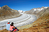 Couple looking towards glacier Grosser Aletschgletscher with Moench, Eiger and Wannenhorn, Grosser Aletschgletscher, UNESCO World Heritage Site Swiss Alps Jungfrau - Aletsch, Bernese Alps, Valais, Switzerland, Europe