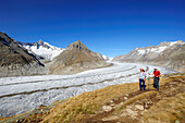 Couple hiking on track above glacier Grosser Aletschgletscher with Aletschhorn, Grosser Aletschgletscher, UNESCO World Heritage Site Swiss Alps Jungfrau - Aletsch, Bernese Alps, Valais, Switzerland, Europe