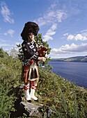 LOCH NESS INVERNESSSHIRE Scottish piper bagpipes tartan kilt uniform lochside near Drumnadrochit