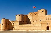 National flag of Oman fluttering over the Jabrin castle, historic adobe fort in the Dhakiliya Region, Sultanate of Oman