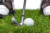 Golf ball in the rough with an iron it behind and the golfers shoes in the background