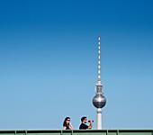 People crossing modern footbridge across Spree River in Mitte Berlin with famous TV Tower to rear