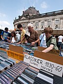 People browsing second hand movies at outdoor weekend flea-market beside Museumsinsel with Bode Museum to rear in Mitte Berlin Germany