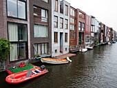 Modern architecture of new houses beside canal on Scheepstimmermanstraat in Borneo Island new property development in Amsterdam Netherlands