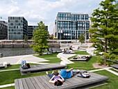 People relaxing at modern Vasco Da Gamma Platz in new Hafencity property development in Hamburg Germany