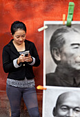Young women with mobile, cellphone, in front of s red wall, picture of Zhou Enlai, former prime minister of China, book market in Ditan Park in Beijing, Beijing, People's Republic of China
