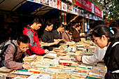 Book market in Ditan Park, Chinese people browsing through books, Beijing, People's Republic of China