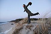 Woman balancing on one food in dunes, Baltic sea spa Ahrenshoop, Mecklenburg-Western Pomerania, Germany