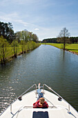 Woman relaxing on the bow of a houseboat near Zechlinerhütte, North Brandenburg Lake District, Brandenburg, Germany