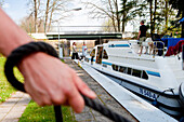 Hand holding a rope to manoeuvre a houseboat through the lock near Zechlinerhütte, North Brandenburg Lake District, Brandenburg, Germany