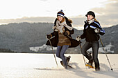 Two young women walking with snow shoe on snow-covered meadow, valley of Leitzachtal, Upper Bavaria, Bavaria, Germany, Europe