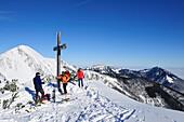 Three people with ski standing at cross on summit of Breitenstein, Geigelstein and Kampenwand in background, Breitenstein, Chiemgau range, Chiemgau, Upper Bavaria, Bavaria, Germany, Europe