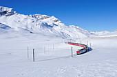 Train of Rhaetien railway driving through winter landscape to Berninapass, UNESCO World Heritage Site Rhaetien Railway, Raetien Railway, Albula-Bernina-line, Bernina range, Upper Engadin, Engadin, Grisons, Switzerland, Europe