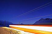 Train of Rhaetien railway driving by night through winter landscape to Berninapass, UNESCO World Heritage Site Rhaetien Railway, Raetien Railway, Albula-Bernina-line, Bernina range, Upper Engadin, Engadin, Grisons, Switzerland, Europe
