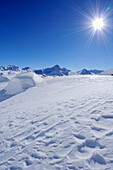 Snow covered boulder with Bernina range in background, Piz Grevasalvas, Albula range, Upper Engadin, Engadin, Grisons, Switzerland, Europe