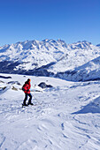 Woman backcountry skiing looking towards Bernina range and lake Silser See, Piz Grevasalvas, Albula range, Upper Engadin, Engadin, Grisons, Switzerland, Europe