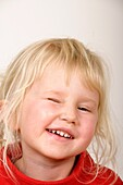 Stock photo of a portrait of a four year old girl looking at the camera and winking
