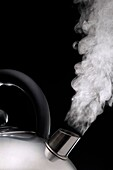 Steaming kettle Against a Black Background