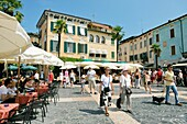 The holiday resort town of Sirmione on Lake Garda, Lombardy, Italy Street cafes on the Piazza Giosue Carducci Lago di Garda