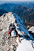Female mountaineer at summit ridge, Montasch, Julian Alps, Friuli-Venezia Giulia, Italy