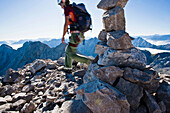Female mountaineer passing Jubilaeumsgrat, cairn in foreground, Wetterstein mountain range, Bavaria, Germany