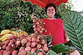 Local woman selling lychees at a stall, La Plaine des Palmistes, La Reunion, Indian Ocean