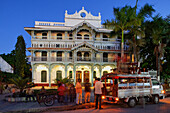 People in front of the old pharmacy at dusk, Mizingani Road, Stonetown, Zanzibar City, Zanzibar, Tanzania, Africa