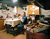Family eating in the kitchen of Venta Rasca, traditional restaurant near San Martin del Pimpollar, Sierra de Gredos, Castile and Leon, Spain