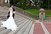 Asian bridal couple on a staircase, posing for a picture, young women doing her exercises next to her dog, Central Park, New York City, United States of America, USA