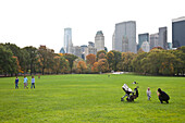 Central Park in aurumn, fall, mother and children, buggy, meadow, grass, Park Avenue, skyscraper, Manhattan, New York City, United States of America, USA