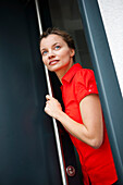 Young woman looking out of a door