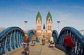 Cyclists passing Wiwili bridge, Church of the Sacred Heart in background, Freiburg im Breisgau, Baden-Wurttemberg, Germany