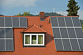 Solar installations on the roof of a private home and wind turbines in the background, Freiburg im Breisgau, Baden-Wuerttemberg, Germany, Europe