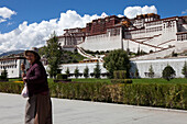 Pilgrim with praywer wheel at the Potala Palace, residence and government seat of the Dalai Lamas in Lhasa, Tibet Autonomous Region, People's Republic of China