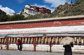 Prayers wheels in front of the Potala Palace, residence and government seat of the Dalai Lamas in Lhasa, Tibet Autonomous Region, People's Republic of China