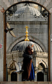 Turkish woman in front of Yeni Valide Camii mosque, Istanbul, Turkey, Europe
