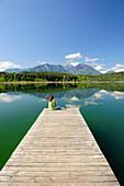 Woman sitting on wooden landing stage at lake Turnersee and looking towards Karawanken range, lake Turnersee, Carinthia, Austria, Europe