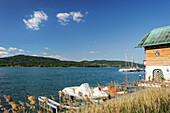 House at lake Woerthersee with wooden landing stage with boats, lake Woerthersee, Carinthia, Austria, Europe
