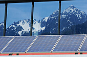 Solar panel on commercial building with windows reflecting mountains, solar plant, photovoltaics, valley of Gailtal, Carinthia, Austria, Europe