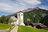 Track leading towards romanesque church St Nicholas, farmhouses in the background, Matrei, East Tyrol, Austria, Europe