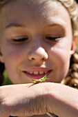 Girl (8 years) with grasshopper on hand