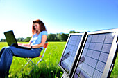 Solar panel producing electricity, woman with laptop out of focus in background, Bavaria, Germany