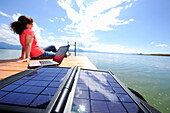 Woman sitting on a jetty at lake Chiemsee, laptop and solar panel in foreground, Chiemgau, Upper Bavaria, Bavaria, Germany